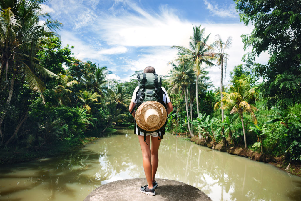 Frau mit Rucksack steht im Amazonas und blickt in die Ferne