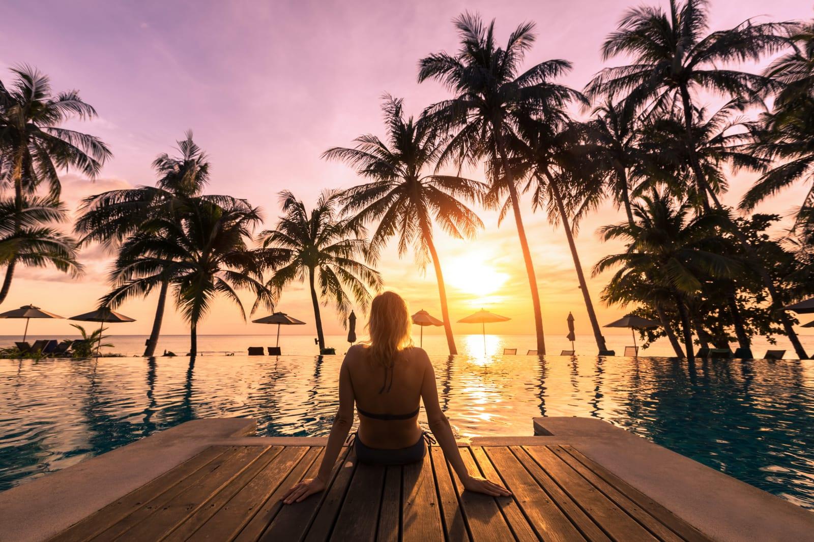 Une femme assise sur une promenade au bord d'une piscine