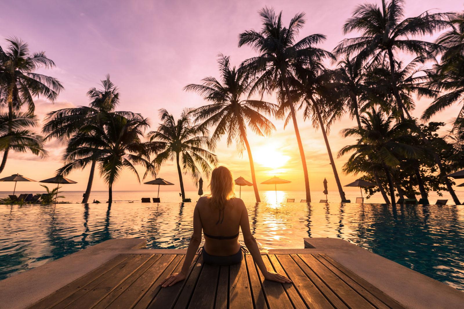 Eine Frau am Pool und Palmen bei Sonnenuntergang Thailand