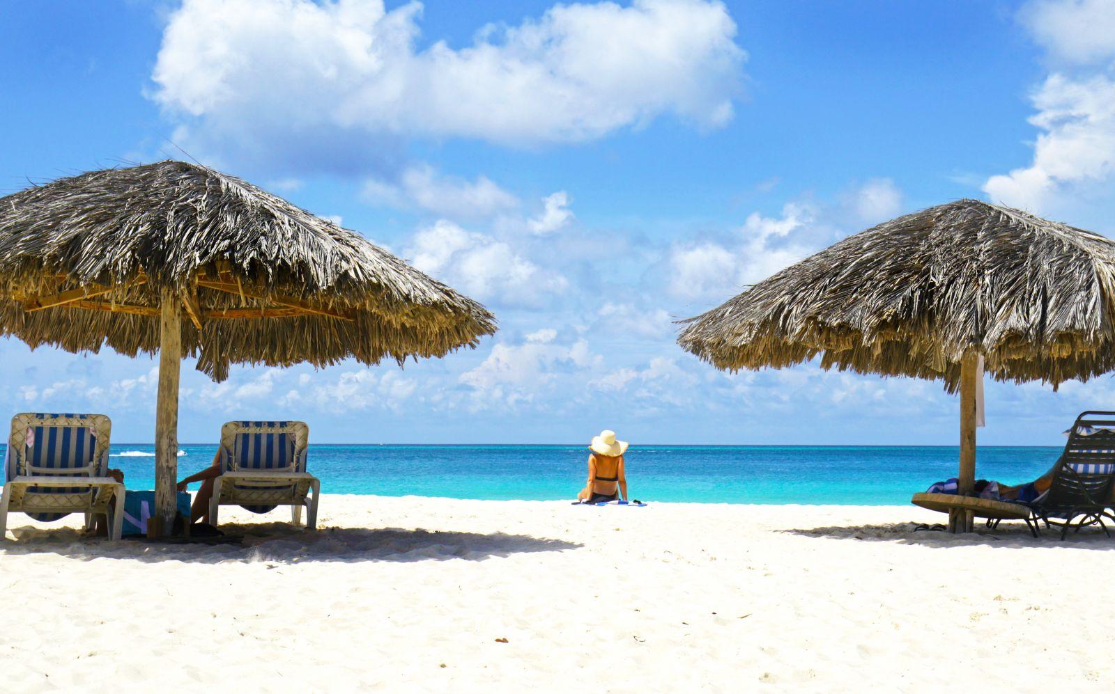 Weißer Strand und tiefblaues Meer in Aruba, Schirme und Strandliegen