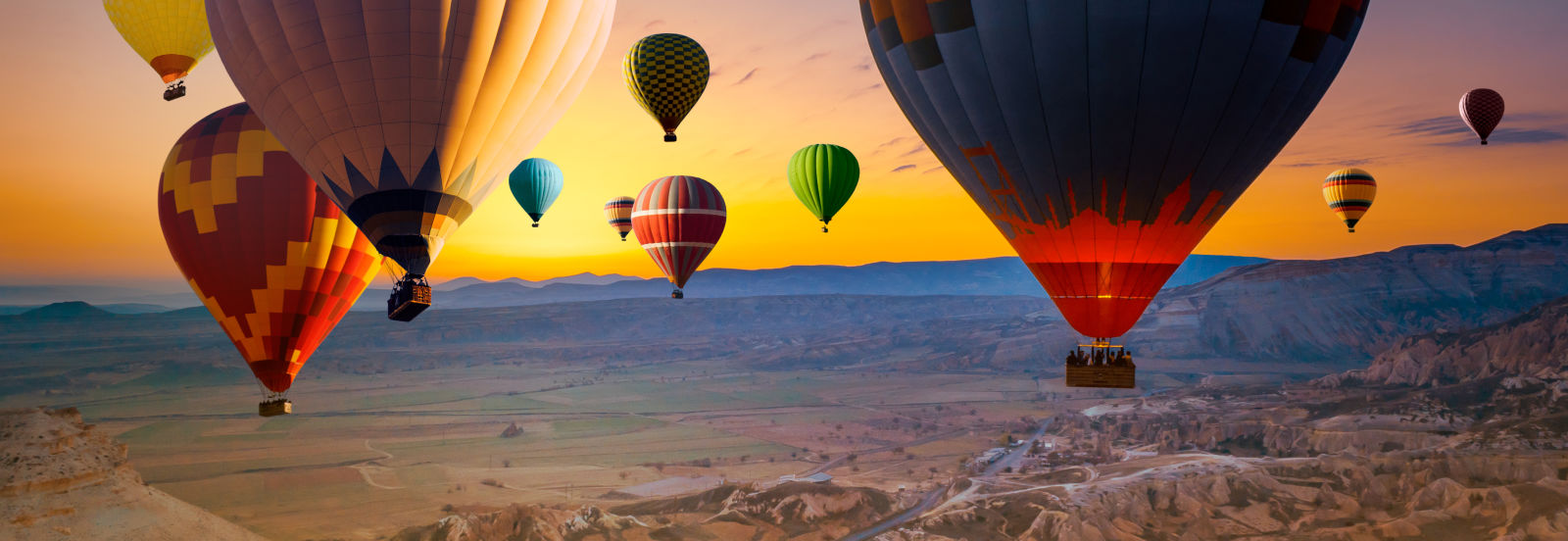 Heißluftballons schweben über einer Berglandschaft in der Türkei