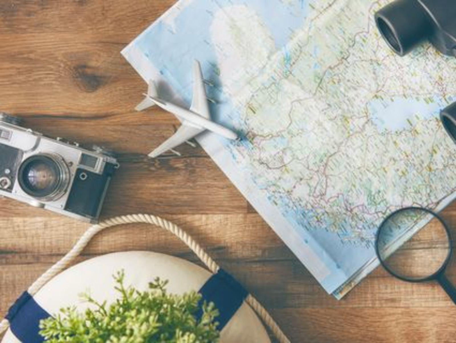 Landkaart, fotocamera, vliegtuig, verrekijker en loop liggen op tafel