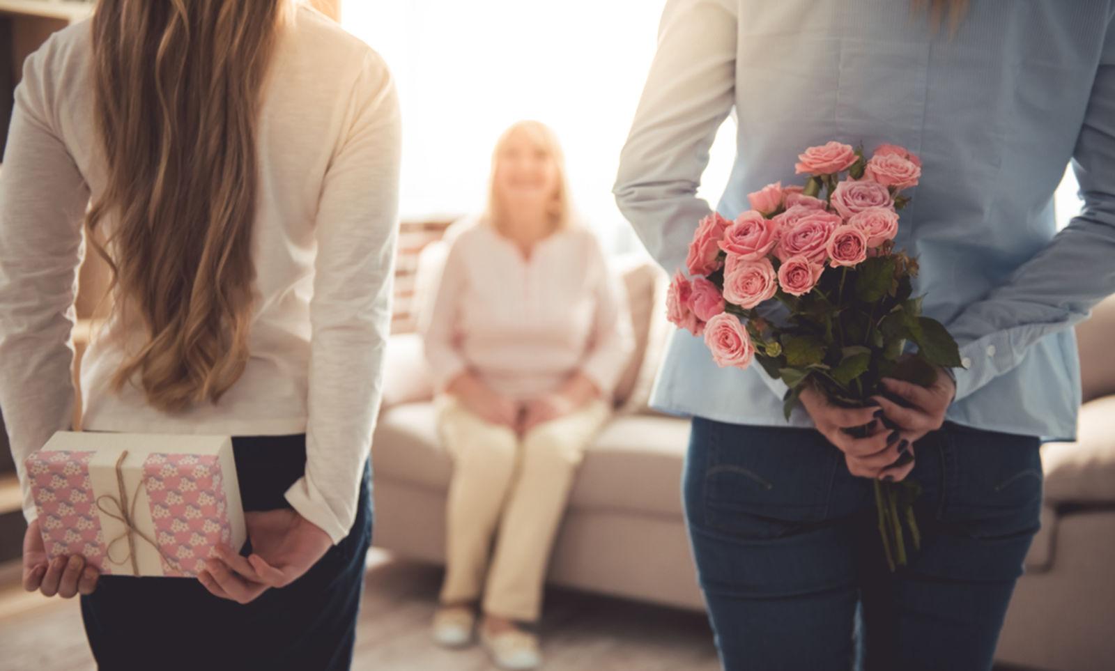 Teenagermädchen und ihre Mutter verbergen Blumen und eine Geschenkbox für ihre wunderschöne Oma hinter Rücken, während Großmutter zu Hause auf der Couch sitzt