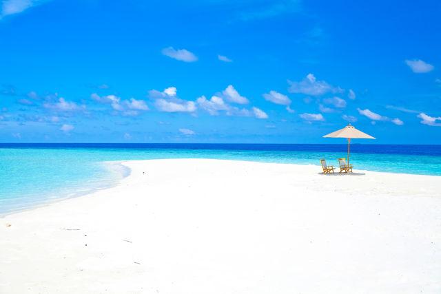Un banc de sable avec parasol et chaises aux Maldives