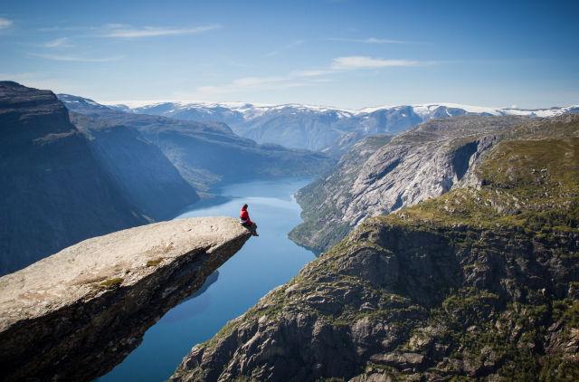 Mann sitzt auf der Trolltunga, Norwegen