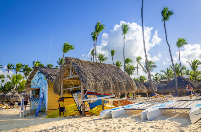 Kajaks, Segelboote und Katamarane an einem karibischen Strand