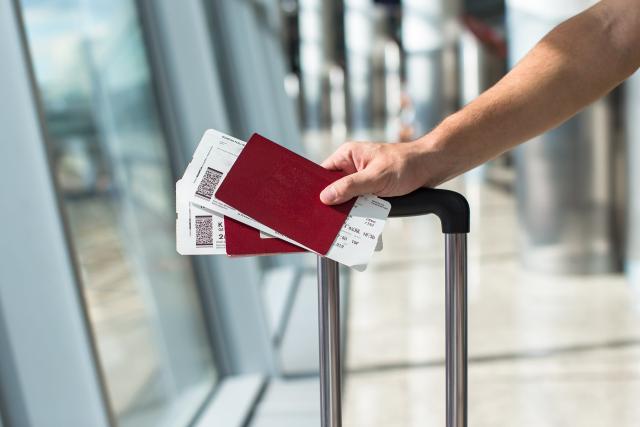 Une personne détient deux passeports et une valise à l'aéroport
