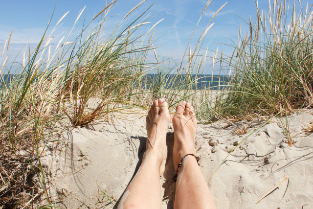 Woman's feet lying in the sand on a dune on a sunny day on the island of Texel, The Netherlands.