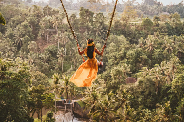 Vrouw in gele jurk op hoge schommel tussen de palmbomen op Bali