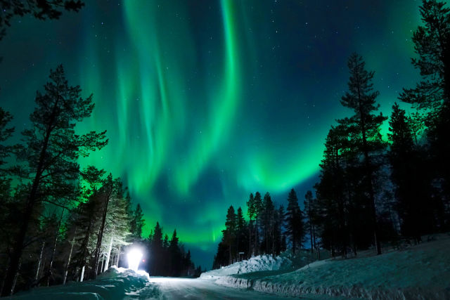 Snowy road in the woods in Lapland under Northern Lights