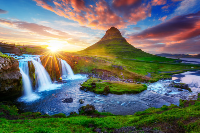 Waterfall in front of mountain in Iceland during sunrise