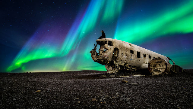Guy sitting on destroyed airplane under the northern lights in Iceland